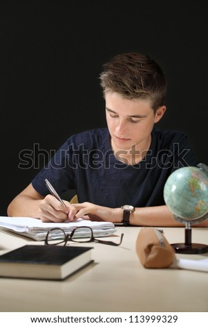 Photo of a young teenager doing his homework in a dark room. - stock photo