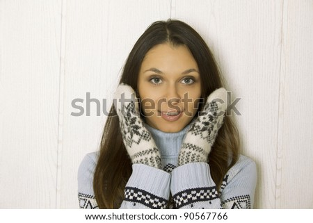Photo of a young woman in soft sweater and mittens, holding her head between her hands