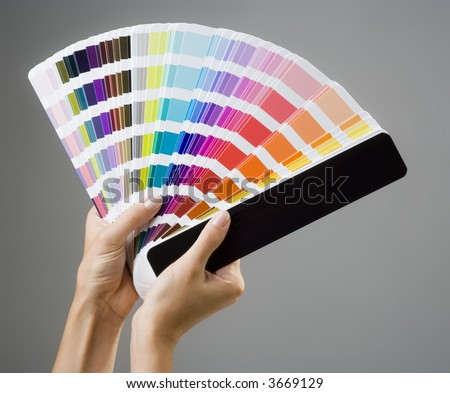 Photo of a young woman's hands holding a color guide - stock photo
