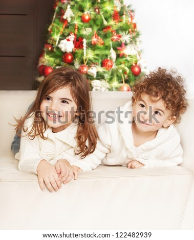 Photo of adorable kids, boy and girl laying down on the sofa and laughing, family at home celebrate Christmas, little babies playing indoor, infant Xmas party, decorated Christmas tree for children - stock photo