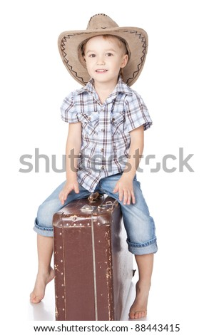 Photo of adorable little boy sitting on suitcase in big hat over white