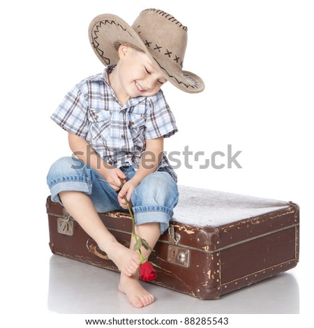 Photo of adorable little boy sitting on suitcase with a rose in hands on white