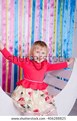 photo of Adorable little girl having fun on a swing.