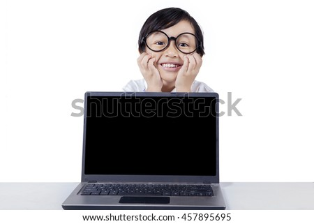 Photo of adorable little girl smiling on the back of laptop with empty screen, isolated on white background