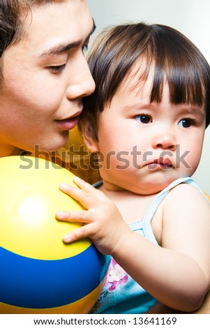 Photo of adorable small girl holding the ball with her daddy near by - stock photo
