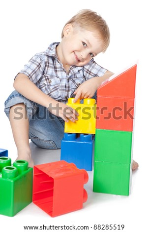 Photo of adorable young boy playing with building blocks over white
