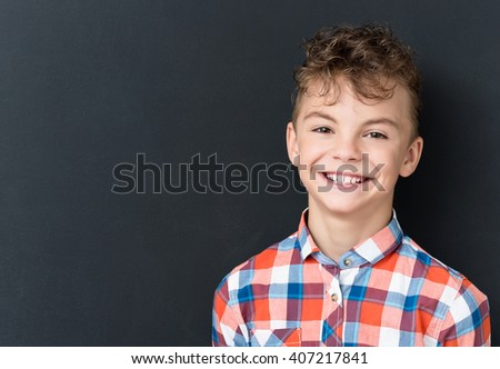 Photo of adorable young happy boy looking at camera at the black chalkboard in classroom. - stock photo