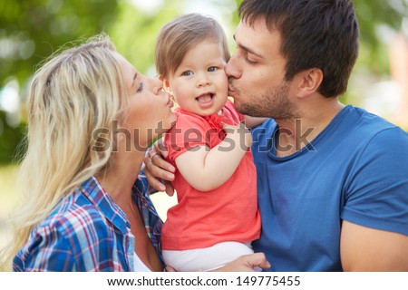 Photo of affectionate parents kissing their small daughter - stock photo