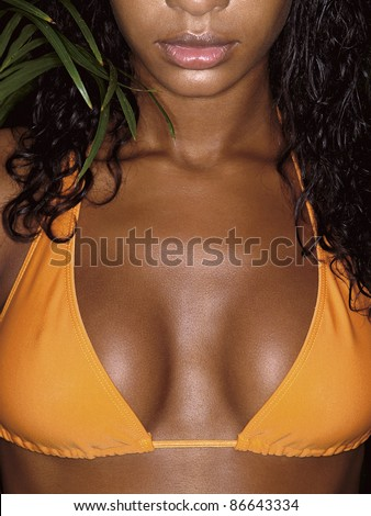 photo of african girl breasts in orange bikini with tropical plant behind - stock photo