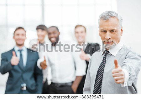 Photo of aged businessman and his colleagues. Businessmen and business woman working in office with big window. Men and woman showing thumbs up and looking at camera - stock photo