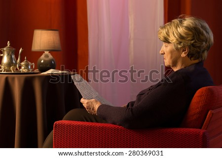 Photo of aged lonely sad woman reading the old letter - stock photo