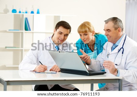Photo of aged physician pointing at laptop display with two colleagues near by looking at it - stock photo