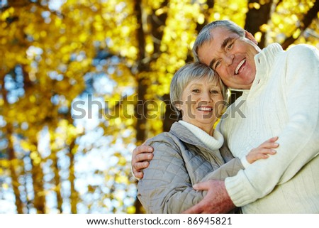 Photo of amorous aged man and woman looking at camera in autumnal park
