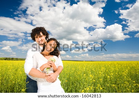 Photo of amorous couple wearing white clothes standing in meadow full of yellow flowers while handsome guy embraces pretty girl tenderly