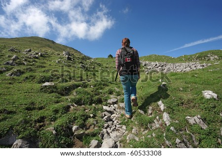 Photo of an active female with backpack hiking up a mountain trail. Slight motion blur on hiker. - stock photo