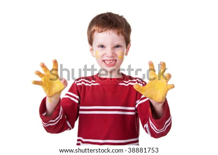 Photo of an adorable child playing with yellow paint.