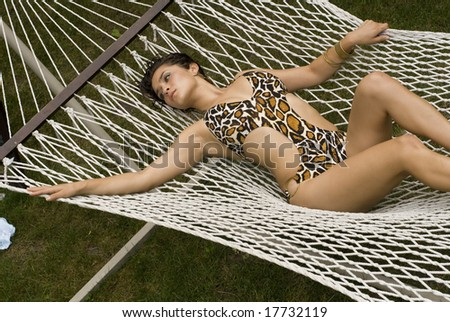 Photo of an adult female's clothed body laying on a white hammock on a sunny day - stock photo