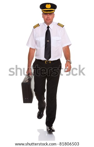 Photo of an airline pilot wearing the four bar Captains epaulettes walking towards camera carrying his flight case, isolated on a white background. - stock photo