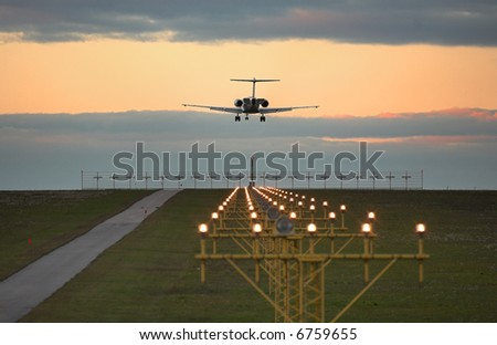 Photo of an airplane just before landing. Runway lights can be seen in the foreground. - stock photo