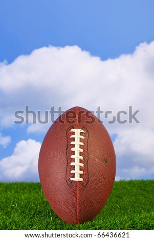 Photo of an American football tee'd up on the grass