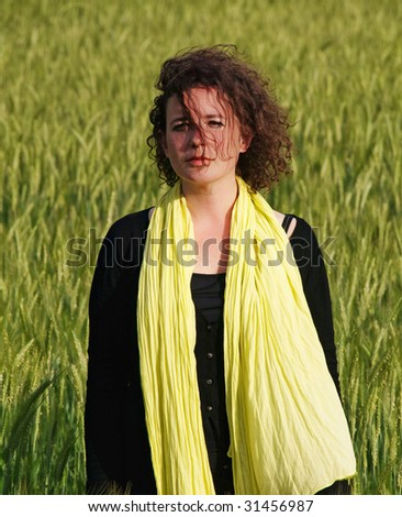 Photo of an attractive french woman wearing a yellow scarf standing in a green barley field