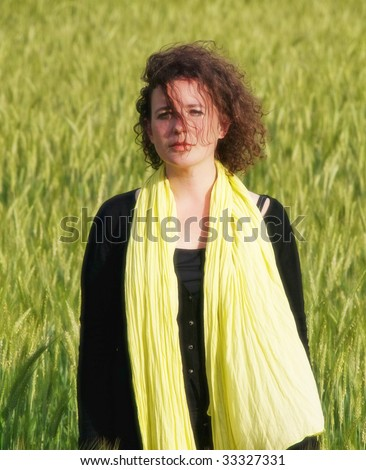 Photo of an attractive french woman wearing a yellow scarf standing in a green barley field orton processed