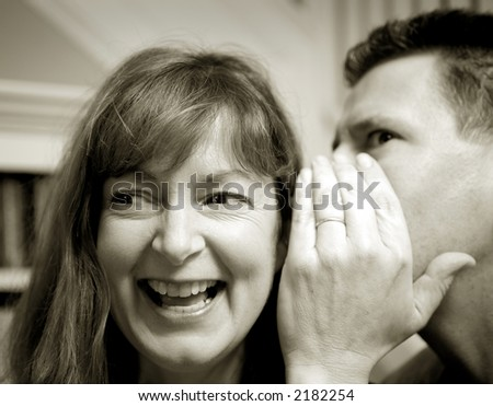 Photo of an attractive man telling a woman a surprising secret.