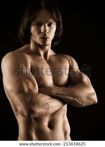 Photo of an attractive young muscular man with no shirt posing with his arms crossed. - stock photo