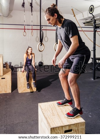 Photo of an attractive young woman and man working out doing jumps at a gym. - stock photo
