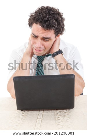 Photo of an desperate and sad caucasian business man frustrated with work sitting in front of a laptop with his hands around the neck. Stiffness, back pain and neck pain due to work - stock photo