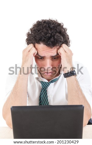Photo of an desperate and sad caucasian business man frustrated with work sitting in front of a laptop with his hands on head - stock photo