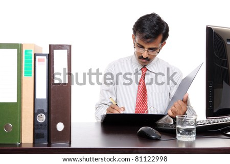 Photo of an Indian male at work sitting in front of the files