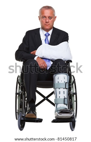 Photo of an injured businessman sitting in a wheelchair, isolated against a white background. - stock photo