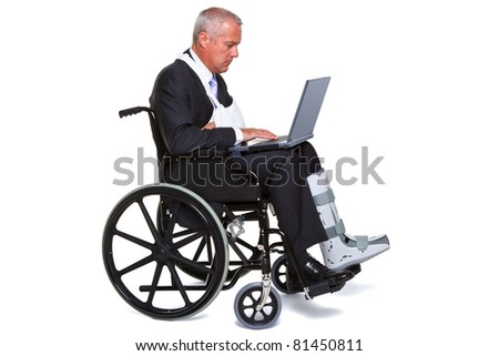 Photo of an injured businessman sitting in a wheelchair working on a laptop computer, isolated against a white background. - stock photo