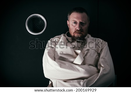 Photo of an insane man in his forties wearing a straitjacket standing in a cell of an asylum with the light from the hallway streaming in. - stock photo