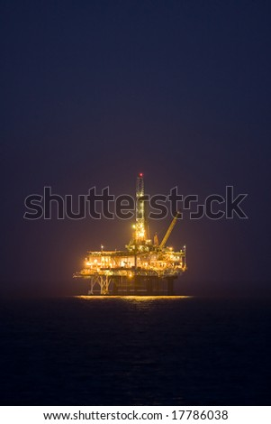 Photo of an offshore drilling rig off the coast of a city in the the US at night.