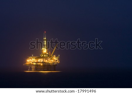 Photo of an offshore drilling rig off the coast of a city in the the US at night - landscape. - stock photo