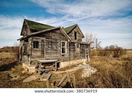 Photo of an old scary abandoned farm house that is deteriorating with time and neglect. - stock photo
