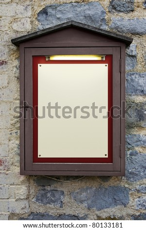 Photo of an old weathered illuminated notice board on a wall, plenty of copy space to add your own text. - stock photo