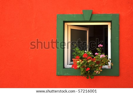 Photo of an opened green window with flowers,