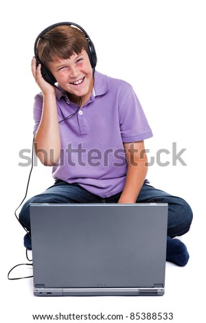 Photo of an 11 year old school boy wearing headphones sitting with a laptop computer, isolated on a white background. - stock photo