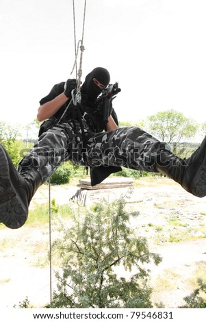 Photo of armed man in combat uniform playing terrorist or special forces team member - stock photo