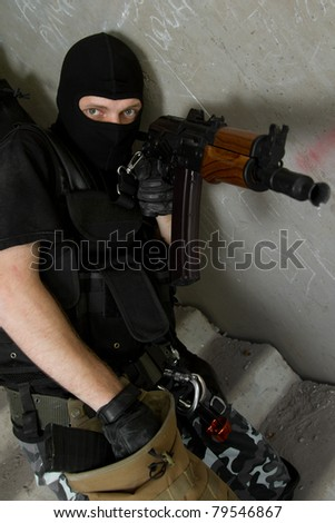 Photo of armed man in combat uniform playing terrorist or special forces team member