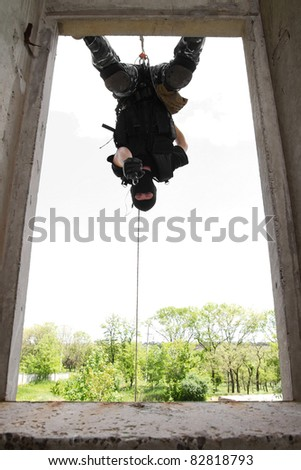 Photo of armed man in combat uniform playing terrorist or special forces team member hanging head down on the rope - stock photo
