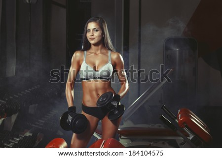 photo of athletic young girl doing a fitness workout with dumbbells in the gym - stock photo