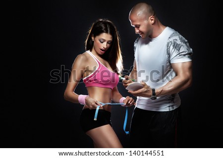 Photo of attractive couple at the gym. Coach measured body of beautiful brunette woman with perfect fitness shape. - stock photo