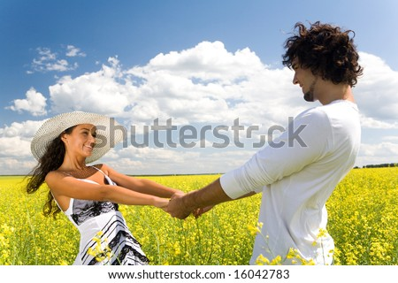 Photo of attractive couple holding by hands and whirling on the meadow at leisure - stock photo