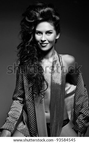 Photo of attractive smiling beautiful woman with magnificent hair and sweet smile posing on dark background - stock photo