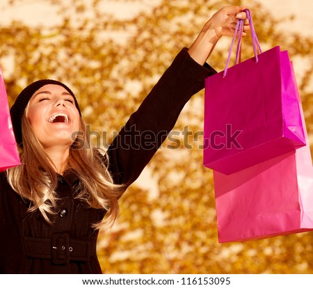 Photo of attractive woman expressing joy of her new purchase, happy good looking girl with pink shopping bags walking in autumn park, money spending and  antistress concept, autumnal sale - stock photo