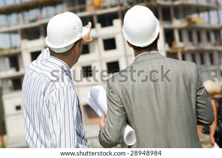 Photo of backs of workers interacting and looking at building